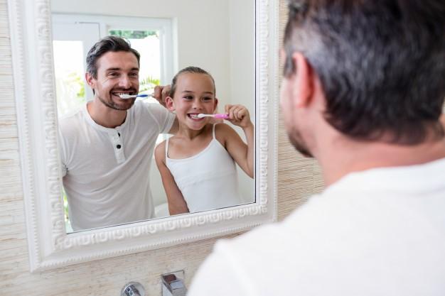 Imagen de un padre y su hija lavándose los dientes en el baño