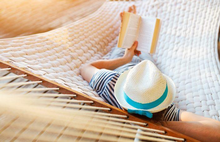 Imagen de una señor leyendo un libro en una hamaca
