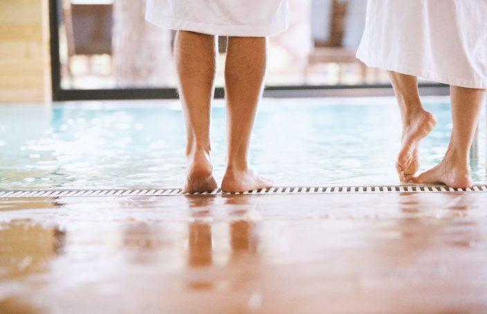 Imagen de dos personas andando descalzas por una piscina, posible origen de los hongos en los pies.