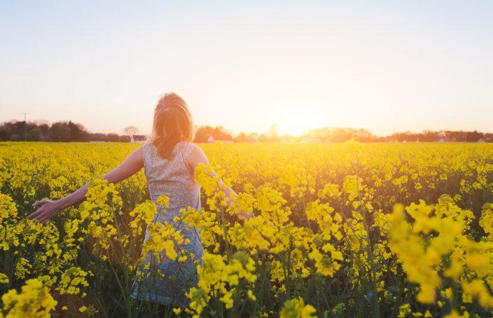 Imagen de una mujer rodeada de un campo de flores