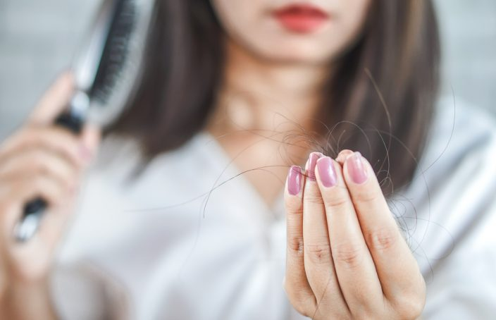 Mujer peinandose que sujeta una gran cantidad de pelo en su mano. Simboliza la caída estacional del cabello